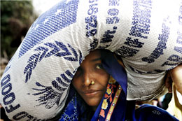 A woman receives food at a distribution in Southern Nepal. Photo: WFP/Laura Melo
